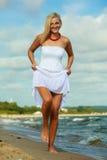 Female tourist walking on beach. Stock Photo