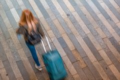 Female tourist walking with her suitcase. Blury female tourist walking with her suitcase stock photo