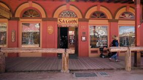 A female tourist walking out of the famous Big Nose Kate Saloon in Tombstone, Arizona