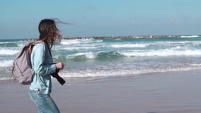 Female tourist walks along summer seashore. Freedom concept. Wind blowing in hair. Sea waves. Slow motion side view. stock video footage