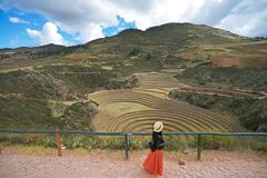 A female tourist who wears a black jacket and an orange skirt is walking on the Inca ruin named `Moray`.Its design creates a tempe royalty free stock images