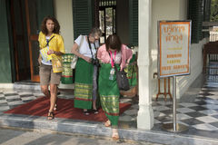 Female tourists at the borrow a sarong venue in Thailand. Tourists borrow a sarong before entering a religious temple as a mark of respect, Sarongs may be stock image