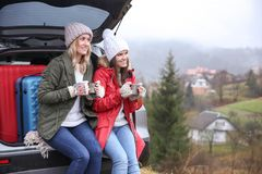 Female tourists drinking hot tea near car. In countryside Royalty Free Stock Photos