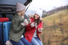 Female tourists drinking hot tea near car. In countryside Stock Images