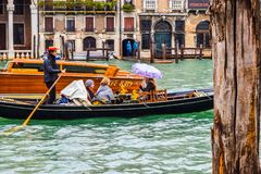 Female tourists on a famous gondola boat ride during rain in the city with Gondolier wearing straw hat, standing with rowing oar. royalty free stock photo