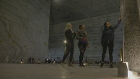 Female tourists having fun while walking among salt walls and sculptures admiring and smelling them in an underground mine -. Female tourists having fun while stock footage