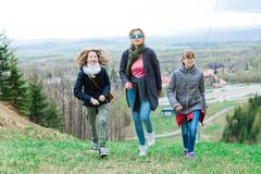 Female tourists reaching top - finishing long uphill trip stock images