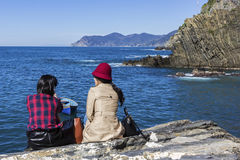 Female tourists sitting on the rock in Riomaggiore in Italy Stock Photos