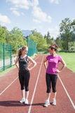 Female Track Competitors Glaring at Each Other. Full Length of Two Adult Woman Standing Side by Side with Hands on Hips in Separate Lanes of Outdoor Running Royalty Free Stock Photography