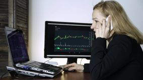 Female trader talking on the phone and watching currency exchange chart at the computer monitor. Work on a crypto stock. Exchange stock footage