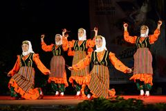 Turkish female dancers performing at a stage. Female traditional dance group from Turkey dancing using wooden spoons for percussion at Summer Theater stage Royalty Free Stock Photo