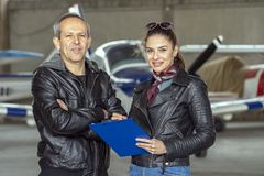 Smiling Woman and Man Pilots in a Hangar. Female trainee pilot and flight instructor standing next to each other and looking at camera. Pilots in front of small royalty free stock photography