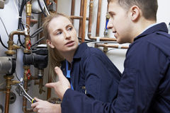 Female Trainee Plumber Working On Central Heating Boiler. Trainee Plumber Working On Central Heating Boiler Stock Image