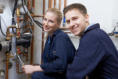 Female Trainee Plumber Working On Central Heating Boiler Royalty Free Stock Photography