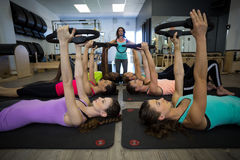 Female trainer assisting group of women with pilates ring exercise. Female trainer assisting group of woman with pilates ring exercise in gym Royalty Free Stock Photo