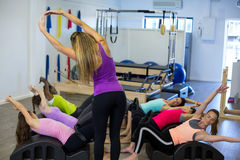 Female trainer assisting group of women with stretching exercise on arc barrel. Female trainer assisting group of woman with stretching exercise on arc barrel in Stock Photos