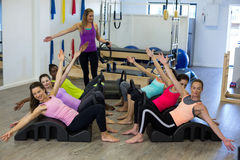 Female trainer assisting group of women with stretching exercise on arc barrel. Female trainer assisting group of woman with stretching exercise on arc barrel in Stock Photo