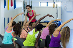 Female trainer assisting group of women with stretching exercise on arc barrel. Female trainer assisting group of woman with stretching exercise on arc barrel in Royalty Free Stock Image