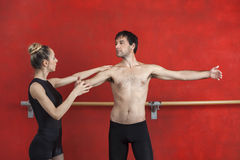 Female Trainer Assisting Male Ballet Dancer In Studio Royalty Free Stock Photo