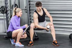 Female trainer assisting man with dumbbells. Female trainer assisting men with dumbbells at crossfit gym Stock Photo
