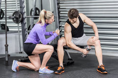 Female trainer assisting man with dumbbells. Female trainer assisting men with dumbbells at crossfit gym Stock Photos