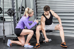 Female trainer assisting man with dumbbells. Female trainer assisting men with dumbbells at crossfit gym Stock Images