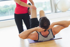 Female trainer assisting man with his exercises in gym Royalty Free Stock Images