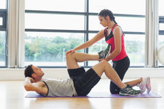 Female trainer assisting man with his exercises in gym Royalty Free Stock Photography