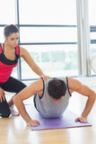Female trainer assisting man with push ups in gym. Female trainer assisting young men with push ups in the bright gym Royalty Free Stock Photography