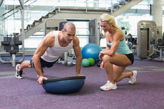 Female trainer assisting man with push ups at gym. View of a female trainer assisting men with push ups at the gym Stock Photography