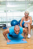 Female trainer assisting man with push ups at gym. View of a female trainer assisting men with push ups at the gym Royalty Free Stock Photo