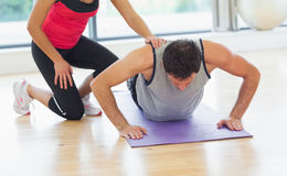 Female trainer assisting man with push ups in gym. Female trainer assisting young men with push ups in the bright gym Stock Photo