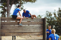 Female trainer assisting man to climb a wooden wall Stock Photography