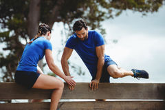 Female trainer assisting man to climb a wooden wall Royalty Free Stock Photography