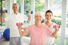 Female trainer assisting senior couple in performing exercise. At home Stock Photo