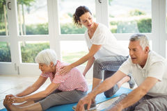 Female trainer assisting senior couple in performing exercise. At home Royalty Free Stock Photography