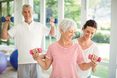 Female trainer assisting senior couple in performing exercise. At home Stock Photos