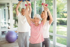 Female trainer assisting senior couple in performing exercise. At home Stock Photography