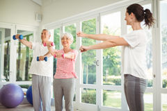 Female trainer assisting senior couple in performing exercise. At home Stock Images