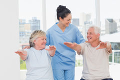 Female trainer assisting senior couple to exercise Stock Image