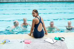 Female trainer assisting senior swimmers at poolside. Portrait of young female trainer assisting senior swimmers at poolside Stock Image