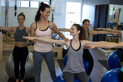 Female trainer assisting woman with exercise. In gym Royalty Free Stock Photography