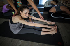 Female trainer assisting woman with exercise. In gym Stock Images