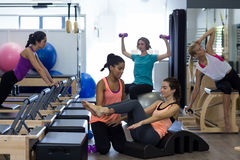 Female trainer assisting woman with stretching exercise on arc barrel Stock Image