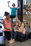 Female trainer assisting woman with stretching exercise on arc barrel Royalty Free Stock Photos