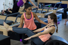 Female trainer assisting woman with stretching exercise on arc barrel Stock Photography