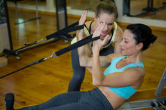 Female trainer assisting woman with stretching exercise Stock Photo