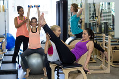 Female trainer assisting woman with stretching exercise on reformer Stock Photography