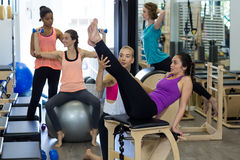 Female trainer assisting woman with stretching exercise on reformer Stock Photos