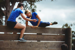 Female trainer assisting woman to climb a wooden wall Royalty Free Stock Photo
